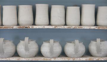 A Shelf of Mugs and Bowls Ready to Glaze